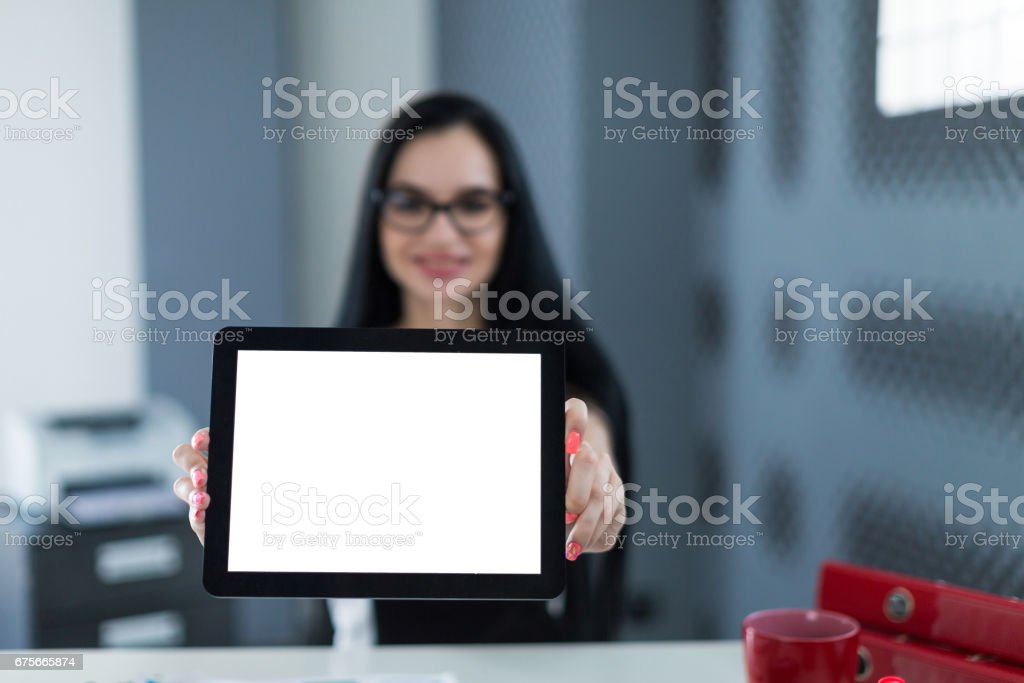 Young cute businesswoman in black dress and glasses sit at the table and show empty tablet royalty-free stock photo