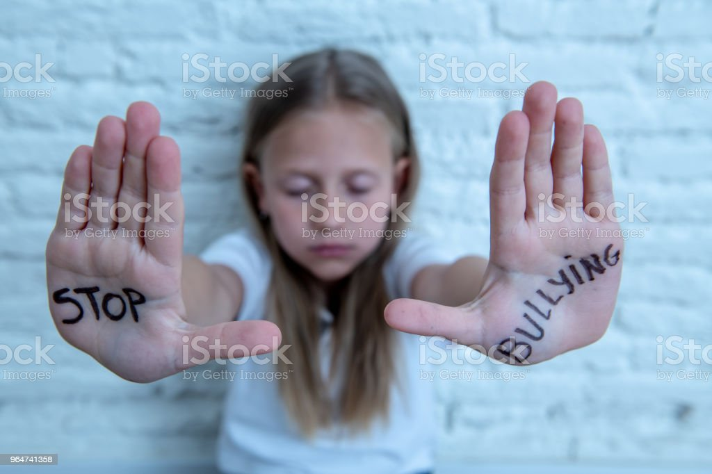 Young cute desperate and scared little schoolgirl showing the text stop bullying written in her hands. Children abused and bullied in school concept. Dramatic light royalty-free stock photo