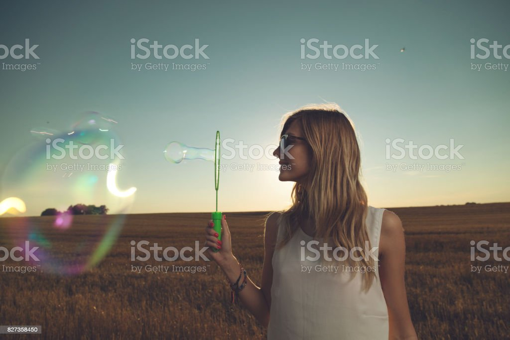 Young cute girl blowing bubbles in nature. stock photo
