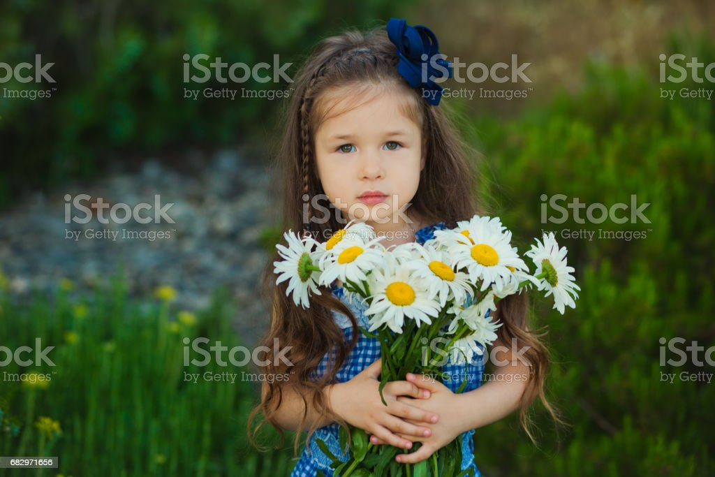 Young cute girl in jeans dress standing close to yellow flowers with basket full of chamomile foto de stock libre de derechos