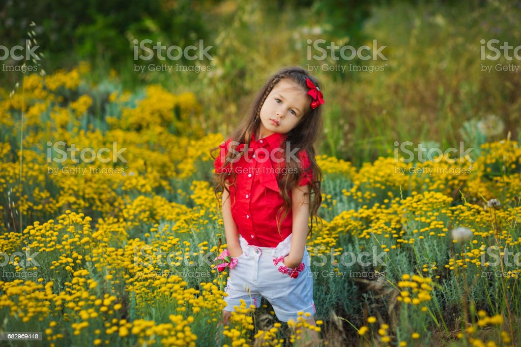 Young cute girl in red shirt and white shorts standing close to yellow flowers royalty-free stock photo