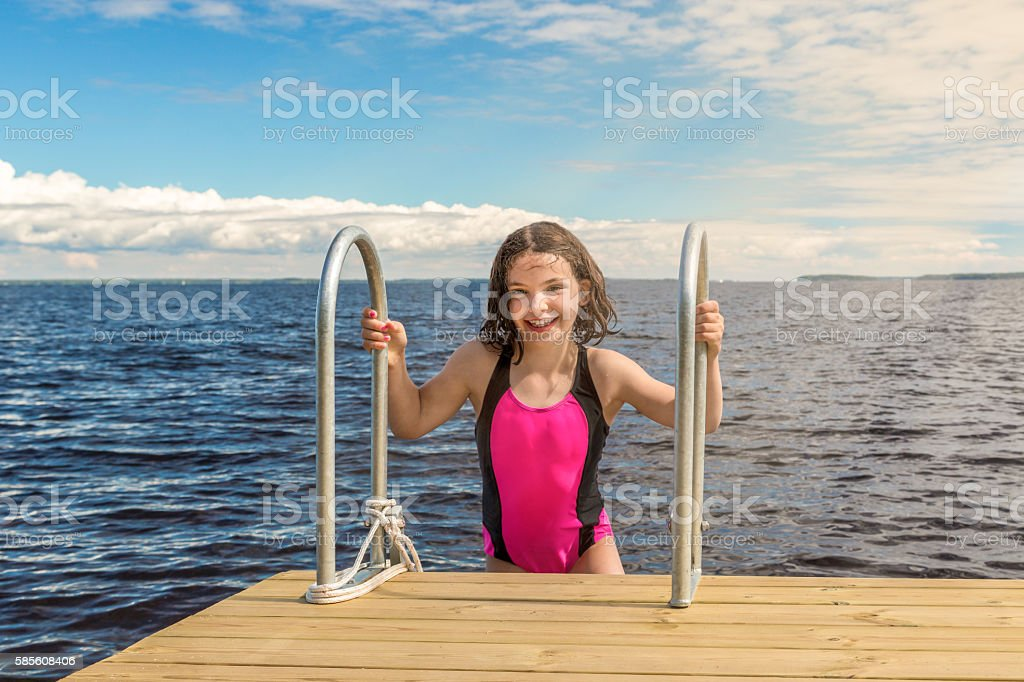 Young cute girl in swimsuit laughing, outdoors on bridge summertime. royalty-free stock photo