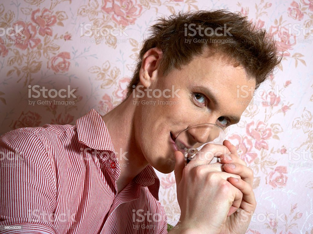 young cute guy tries to drink royalty-free stock photo
