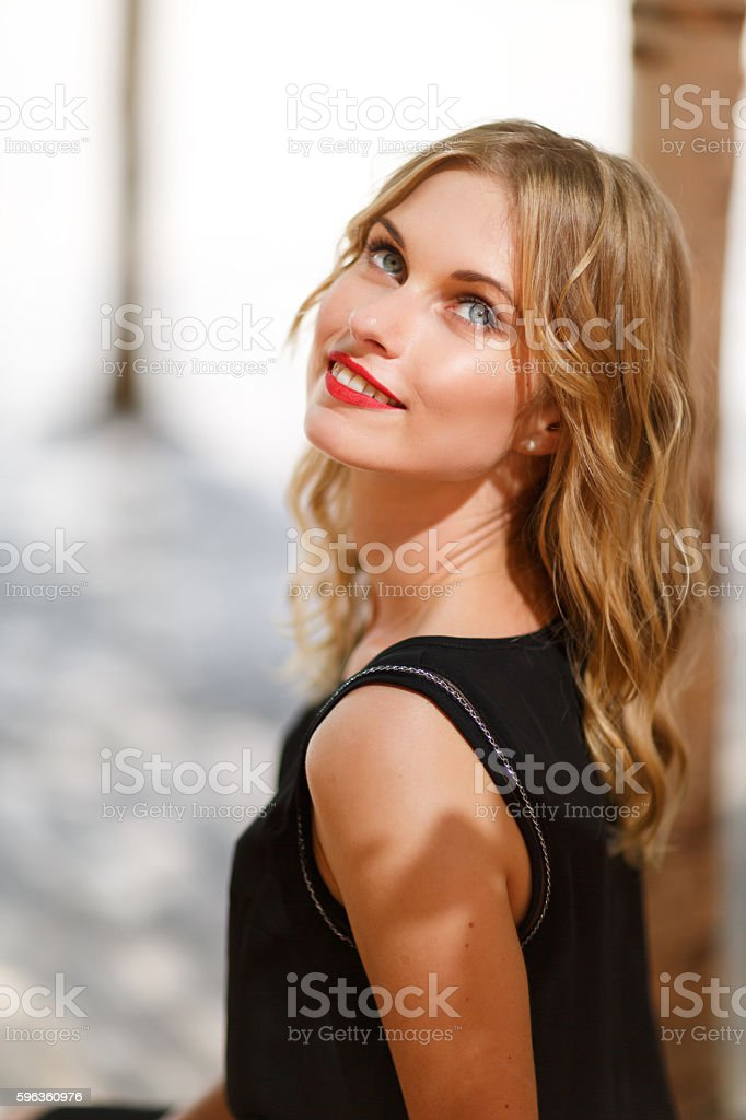 Young cute happy woman with curly blond hair outdoors royalty-free stock photo