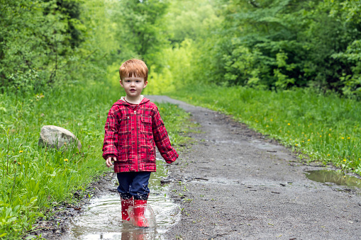 Young Cute Kid Walking Jumping Into Water Puddle Stock Photo - Download Image Now