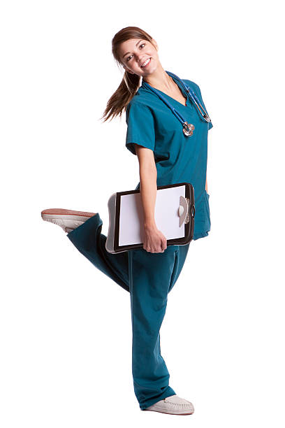 young cute nurse kicking foot back - female nurse stock photos and pictures