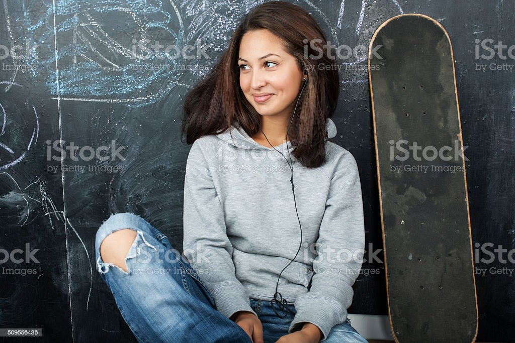 young cute teenage girl in classroom at blackboard seating on stock photo