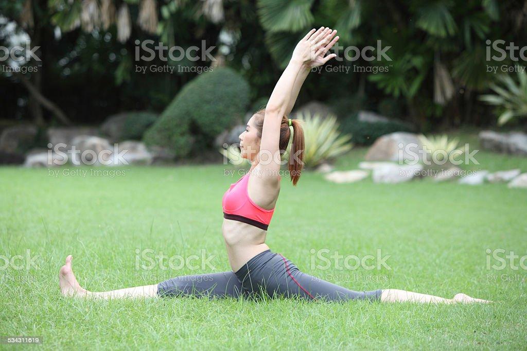 Young cute woman in the Hanumanasana/Monkey Pose on lawn stock photo