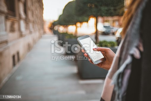 855341616istockphoto Young cute woman using phone 1129840134