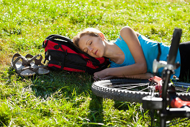 Young cyclist enjoying sleeps relax lying in the fresh grass Young girl cyclist enjoying sleeps relax lying in the fresh grass on spring sunny meadow. Outdoor female biker resting stock pictures, royalty-free photos & images