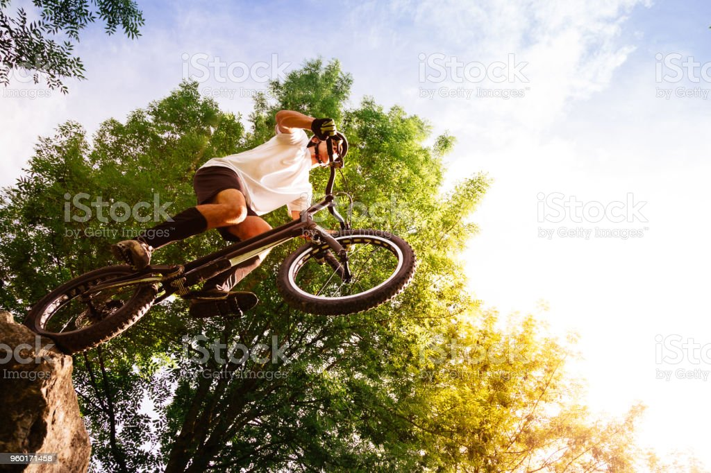 Young cyclist on the edge of a rock ready to jump stock photo