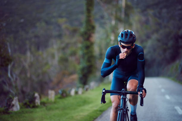 Young cyclist riding bicycle and eating snack bar outdoors stock photo