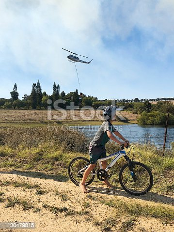 Two Caucasian Cycling boys watching a rescue firefighting helicopter filling a water bucket from a dam lake with the fire cloud of smoke behind near Stellenbosch South Africa