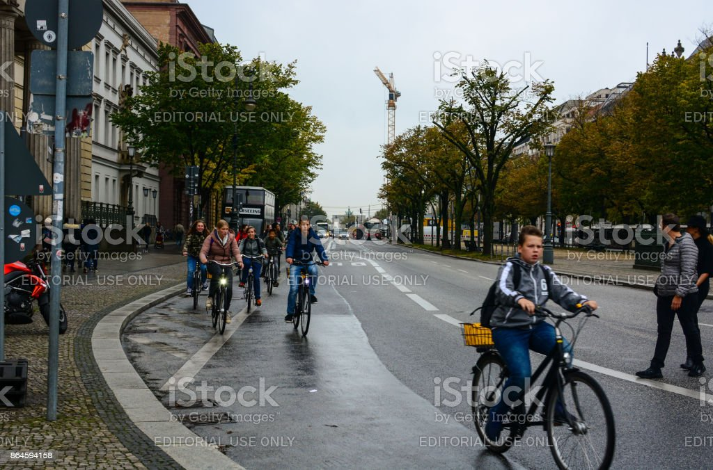 Young cyclists moving from Brandenburg Gate by Unter den Linden boulevard in Berlin, Germany stock photo