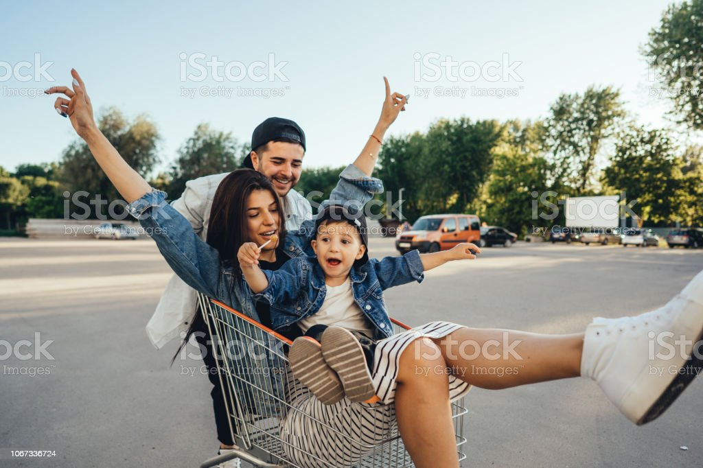 Young dad carries mom and son in a cart on the parking lot stock photo