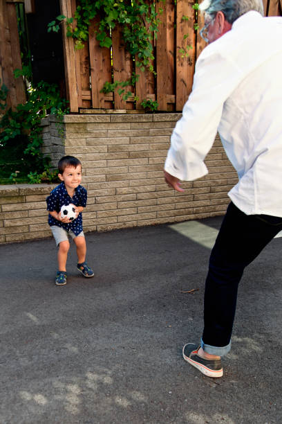 Young dad of 50+ playing with son in driveway stock photo