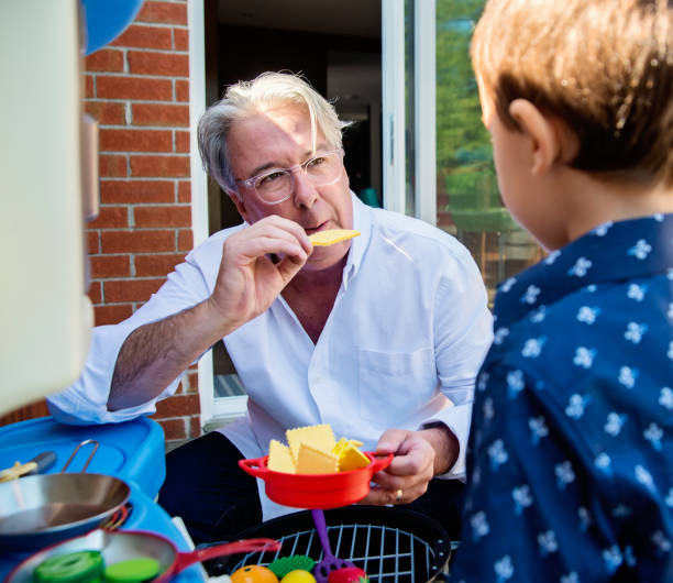 Young dad of 50+ playing with son on home patio stock photo