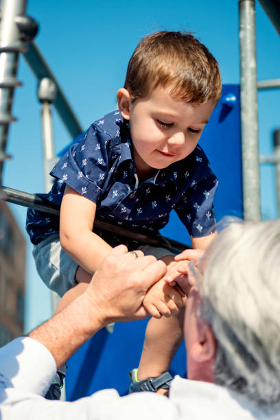Young dad of 50+ playing with son on playground stock photo