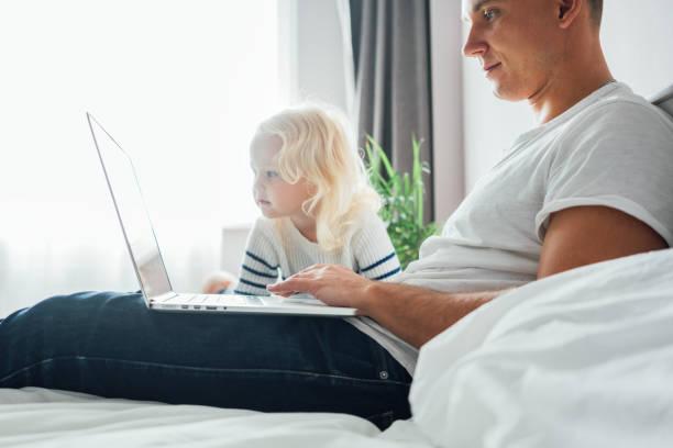 Junge Papa sitzt auf dem Bett mit Kindern mit dem Computer zusammen zu Hause. Vater arbeitet am Laptop, während seine Tochter auf dem Bildschirm schaut – Foto