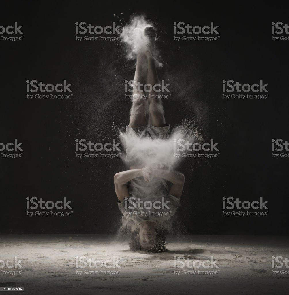 Junge Tänzerin macht einen Kopfstand im Staub-Cloud-Ansicht – Foto