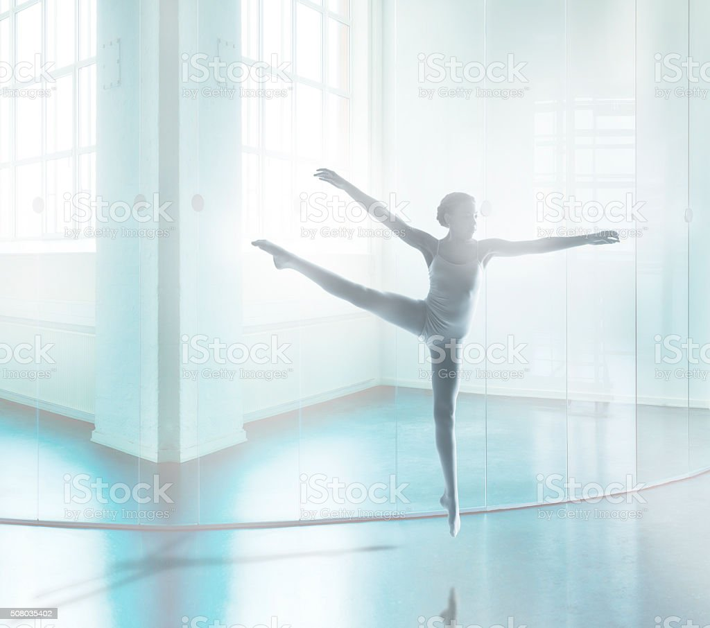 Young dancer jumping in bright interior stock photo