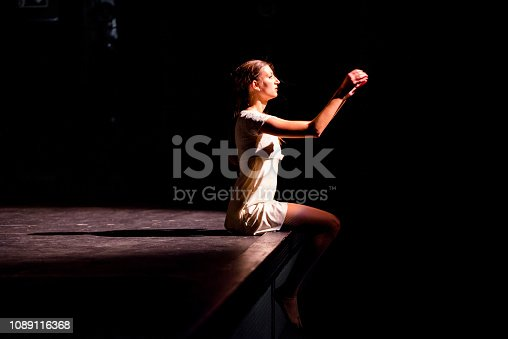 Young caucasian dancer performing on a theater stage.