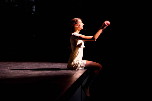 Young dancer performing on a theater stage Young caucasian dancer performing on a theater stage. performing arts event stock pictures, royalty-free photos & images