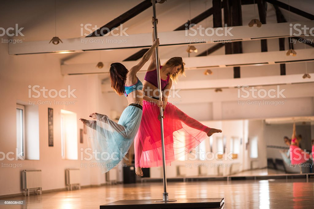 Young dancers dancing on a pole in a studio. stock photo