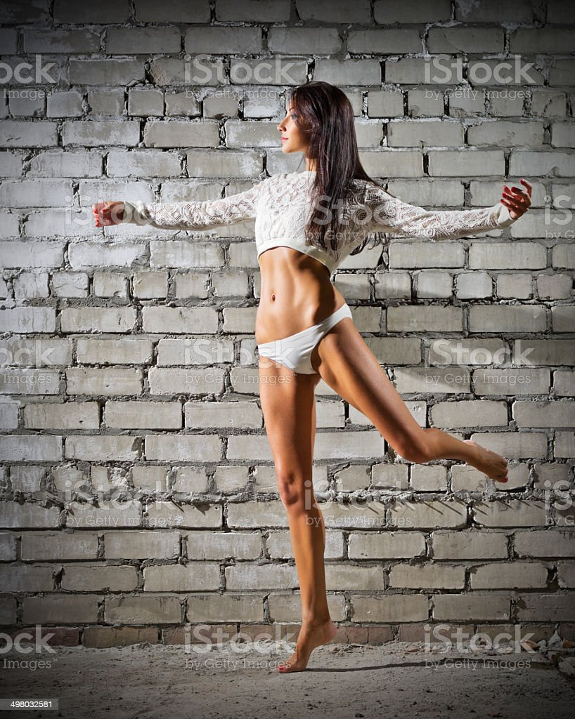 Young dancing woman on brick wall background (normal version) stock photo