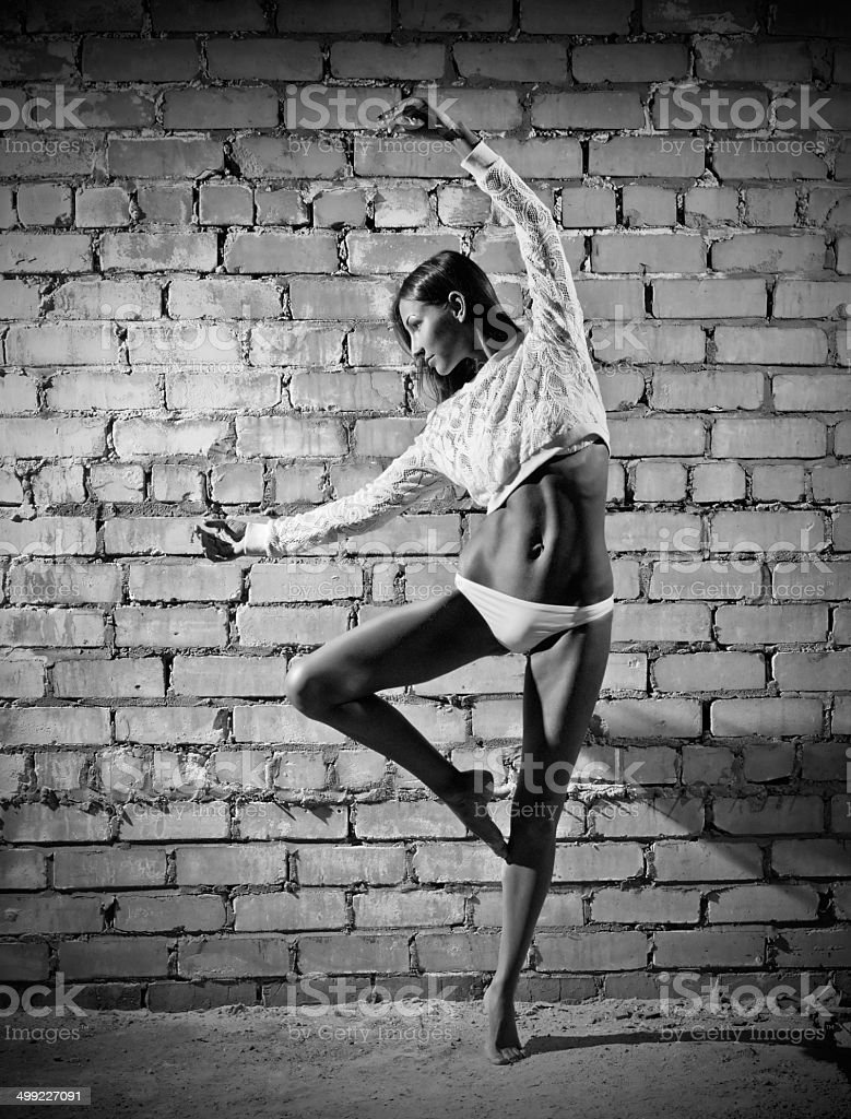 Young dancing woman on brick wall background (monochrome ver) stock photo