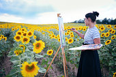 young female dark haired artist painting outdoors with oil colors in sunflower fields wearing long skirt