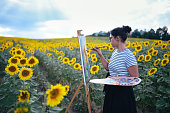 young female dark haired artist painting outside using oil colors in sunflower fields wearing long dress