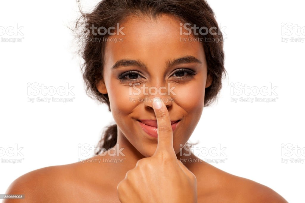 Young dark skinned woman touching her nose stock photo