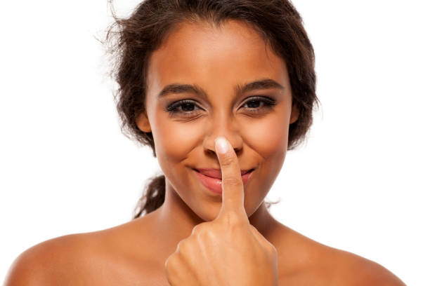 young dark skinned woman touching her nose - naso foto e immagini stock