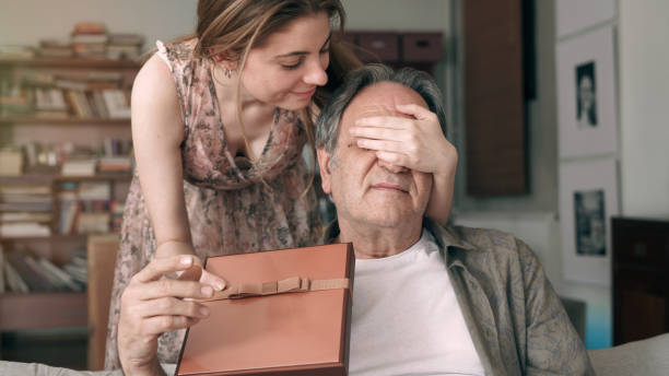 Young daughter embracing her father with love and giving present stock photo