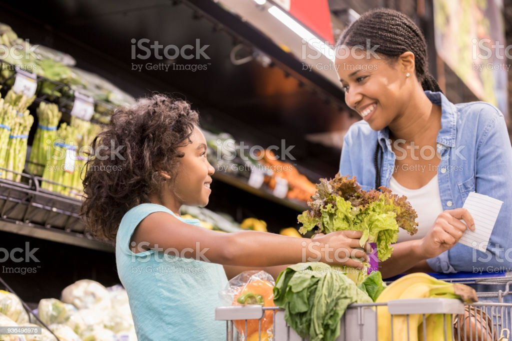 Young daughter helps mom grocery shop stock photo