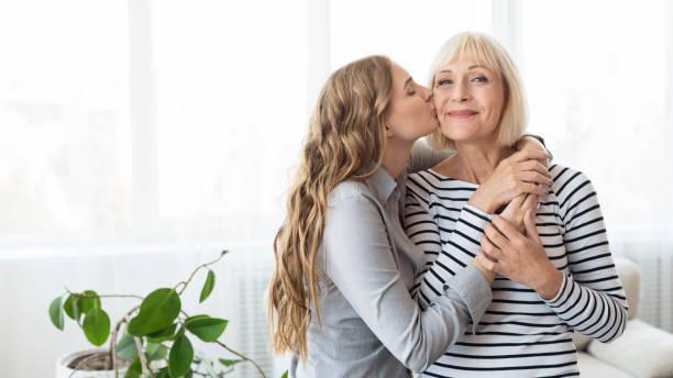 joven hija besando madre mayor en la mejilla - hija fotografías e imágenes de stock