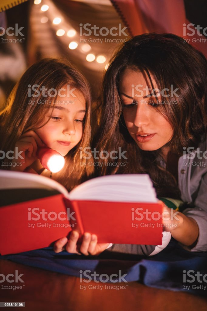 Young daughter listening to a bedtime story by her mother stock photo