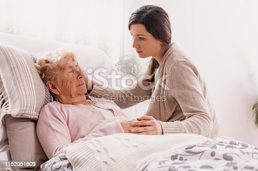 istock Young daughter supporting sick mother lying in hospital bed 1152051809