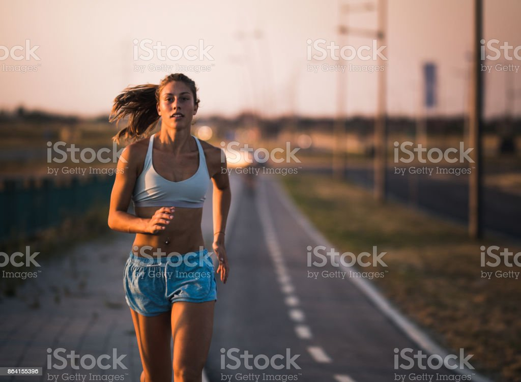 Young dedicated female athlete running on the street. royalty-free stock photo