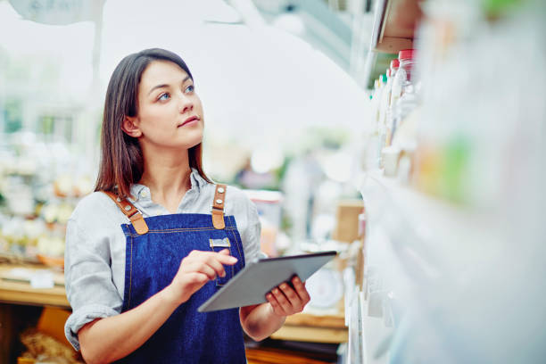 Young deli owner holding digital tablet while standing in store stock photo