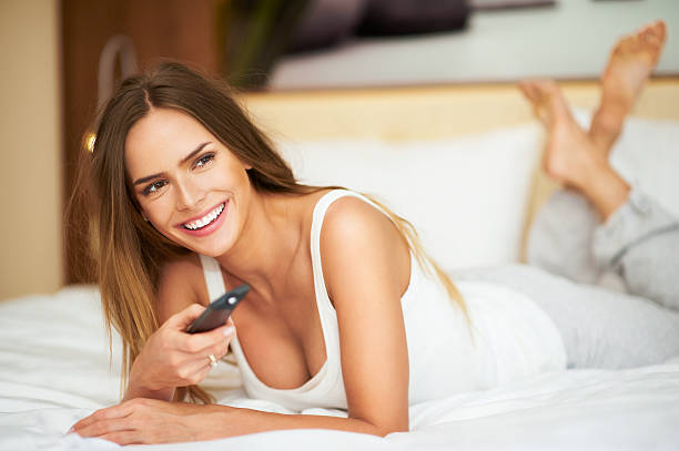 Young delicate beautiful woman laying on bed with remote control stock photo