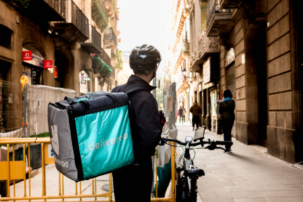 young Deliveroo delivey service company by bike in the streets of city working during the day stock photo