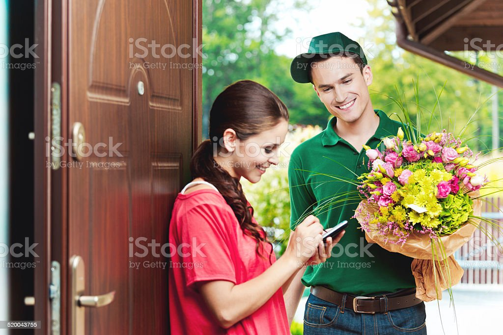 Young delivery man delivering flowers Smiling delivery man delivering a bouquet of flowers for young woman, standing in th entrance house door and woman signing up on the palmtop.  20-24 Years Stock Photo