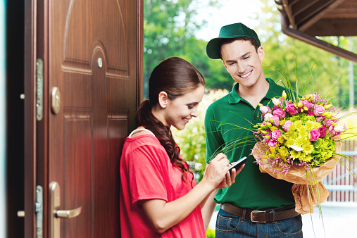Young Delivery Man Delivering Flowers Stock Photo - Download Image Now