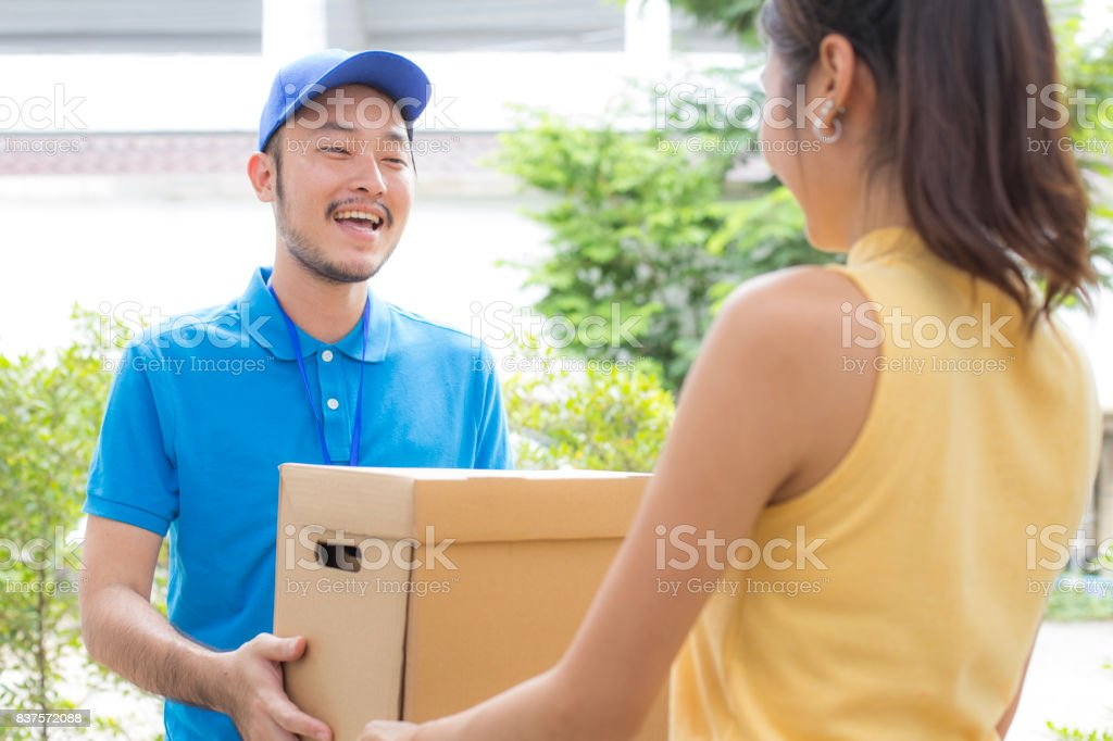 Young Delivery Man giving a Cardboard Box to Woman with Attractive smiling at Home. Delivery Concept. stock photo