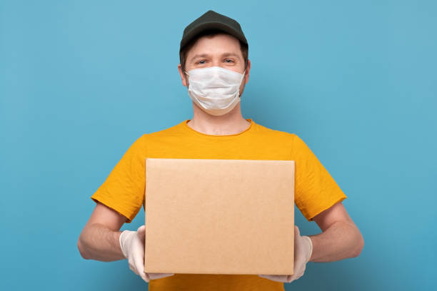 Young delivery man in nedical mask holding and carrying a cardbox on blue wall stock photo