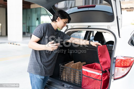 Hispanic delivery man removing parcel from backpack in car trunk