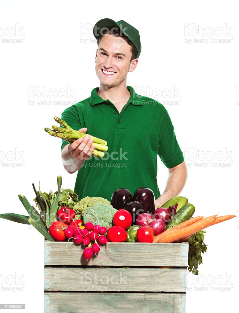 Young delivery man with organic food Delivery man wearing green cap and t-shirt, delivering box with organic food, holding asparagus in hand and smiling at the camera. Studio shot, white background. Adult Stock Photo