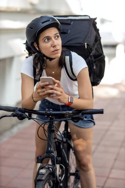 young delivery woman checking delivery address on mobile app - dodatkowa praca zdjęcia i obrazy z banku zdjęć